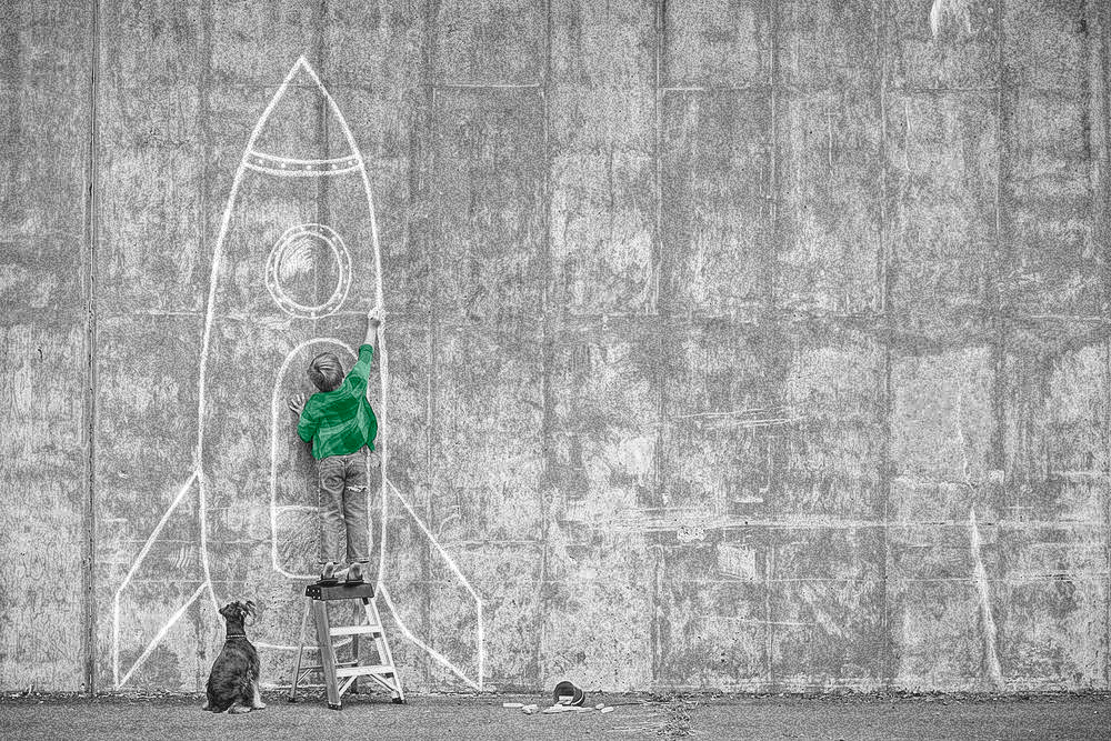 Don't keep your talent in the classroom. Give them the tools to reach the sky (Boy drawing a rocket on a wall, dreaming of working in aviation)